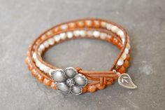"""Double wrap rustic leather bracelet with textured orange marble and ivory shell beads. Antique silver flower button and tribe hill silver paisley charm. ($26)  -Size Md (15""""long) fits a 7"""" wrist  www.facebook.com/kyaracreations"""