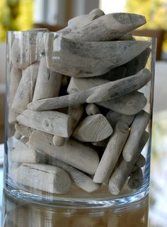Glass vase filled with weathered drift wood.