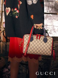 Red and blue leather trim a Gucci Pre-Fall 2016 top handle bag crafted in the House's GG motif with a detachable shoulder strap.