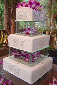 Monogrammed wedding cake with glass pillars filled with flowers. very pretty!!