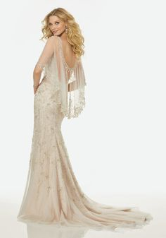 Intricately Beaded Embroidery on a V-Neck, Slim Tulle Gown with Dramatic, Beaded Tulle Modified Capelet. Find this wedding dress and more unique styles exclusively at Bridal Boutique of Arizona in Midtown Phoenix.