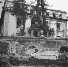 Destroyed military vehicle amid rubble piled outside bullet scarred walls of the home of German Minister of Propaganda Joseph Goebbels, following the fall of the city to allied troops.