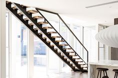chunky 66mm American oak treads, primed black steel strings and a glass balustrade.