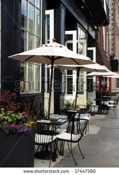 stock photo : Outdoor cafe tables with umbrellas up and places set waiting for customers to arrive