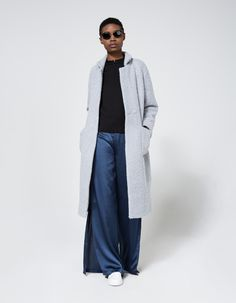 Textured overcoat from Ganni. Available in Black, Smoked Pearl or Quarry. Pointed collar with notch lapel. Open front with dual snap button closure at waist. Detached tie belt. Dual front patch pockets. Interior left chest pocket. Lined.   • Textured wo