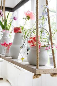 flowers on the display in a rustic wooden hanging unit