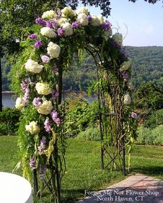 Arch decorated with purple and white flowers and greens for an outdoor wedding ceremony. By Forget Me Not Flower Shop, North Haven, CT