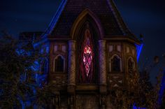 The Evil Queen peeking out from behind the drapes of her window above the entrance to Snow White's Scary Adventure at night in Fantasyland, Disneyland