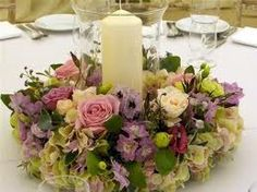 candles in hurricane vases with flowers around for centre pieces.