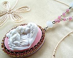 $124 Gorgeous antique 8mm faceted milky white crystal beads, pink glass beads and lavender glass rhinestones around a raised resin pink and white Madonna and Child Jesus raised resin cameo center. The vintage locket is painted a very pale pink. Inside is a large area for pictures, prayer requests, or special intentions to Mother Mary. Can also be displayed on a wall!