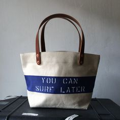 "Vintage made in Japan off white canvas with blue line. Stenciled ""YOU CAN SURF LATER"" IND_BNP_0149 W35.5cm H20.5cm D14cm Handle38cm"