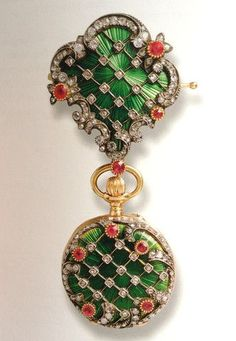 Watch Fob, Carl Faberge Exhibition at Wartski. Composed as a brooch decorated with a vivd green sunburst guilloche enamel, overlaid with diamond set trellis work and a border in the rococo style set with diamonds and rubies. The suspended watch is similarly decorated.