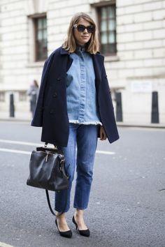Dziewczyna w spodniach z ciemnego denimu i jeansowej koszli oraz wełnianym, eleganckim płaszczu.