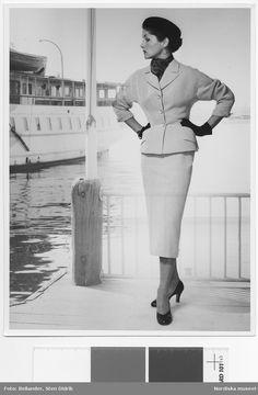 1949-1953. Modell klädd i dräkt, hatt handskar, sjal, örhängen och pumps, vid en kaj. Fotograf: Sten Didrik Bellander