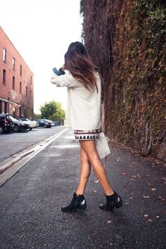 monocolored sweater; patterned skirt, ankle boots
