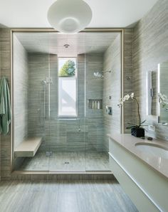 In this modern bathroom, a large walk-in shower has double shower heads and a built-in bench, while the same tile used in the shower has also been used for the walls and floor.
