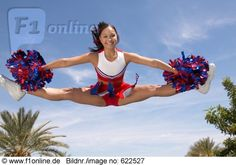 cheerleader in the air | Portrait of a Cheerleader Holding Pompoms Doing the Splits Mid-Air ...