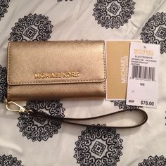 Michael Kors Wristlet Brand new, with tags. Pale gold Michael Kors phone case for iPhone 5 or 5C. Has slots for cards. 100% authentic. Would make the perfect gift! Michael Kors Bags Clutches & Wristlets