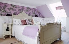 Attic bedroom with patterned wallpaper and dormer window