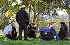 Amish men waiting near crime scene tape after Nickel Mines school shooting.