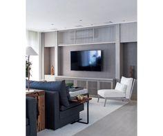 As arquitetas Andrea Teixeira e Fernanda Negrelli esconderam o aparelho numa área (2,60 m x 40 cm x 40 cm*) acima do painel da TV (Defnitiva Móveis), atrás de uma porta ripada com vãos de 2,5 cm.