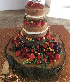 Delicious Naked Wedding Cake with Fresh Berries on Wood Log