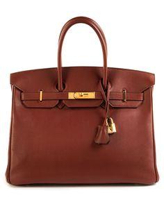 Ca. 25 x 35 x 18 cm. Handtasche aus dunkelrotem Kalbsleder mit goldfarbenen Beschlägen. Originalschloss, Schlüsselpaar und Clochette sind vorhanden. Innenraum...
