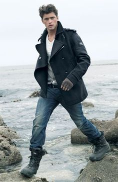 Pairing a black pea coat with navy blue jeans is an on-point option for a day in the office. Finish off this look with dark grey leather boots.  Shop this look for $239:  http://lookastic.com/men/looks/v-neck-t-shirt-cardigan-pea-coat-belt-gloves-jeans-boots/5098  — White V-neck T-shirt  — Grey Cardigan  — Black Pea Coat  — Black Leather Belt  — Grey Wool Gloves  — Navy Jeans  — Charcoal Leather Boots