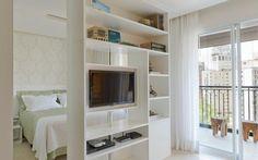 Desenhada pela arquiteta, a estante semivazada divide sala e quarto de maneira sutil. A TV com sistema rotativo pode ser vista nos dois ambientes. Foto: Divulgação / Inês Antick