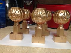 Pumpkin Trophies Made with small plastic pumpkin buckets and bubbles from Party City and two small wooden blocks. Glued all together and spray painted it gold.