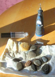 After carving river rocks with a dremel, rub with bees wax and glue a magnet on the back with two-part epoxy.