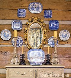 Blue and white antique china plates and a gilded mirror hanging on log walls. Where rustic meets refined. Blue And White China, Blue China, Grand Cadre Photo, Casas Magnolia, Log Wall, Plate Display, Dish Display, Enchanted Home, Blue Plates