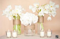 Des vases transparents enroulés de ficelle avec des fleurs blanches et des petites bougies.