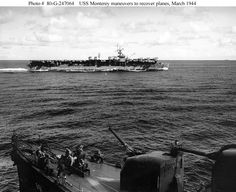 """Maneuvers to recover planes during operations in the New Guinea area, March 1944. Photographed from USS Erben (DD-631), the USS Monterey (CVL-26) is in the background. Note details of her forward 5""""/38 gun mount and crewmen lounging on her foredeck on USS Erben."""