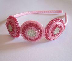 Tiara forrada com fita de cetim e 3 enfeites bordados de vitrilhos em tons de rosa.