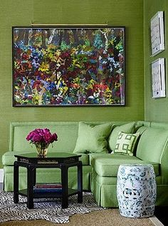 Inside A Palm Beach Bermuda-Style Bungalow - The Glam Pad~A custom-designed banquette, topped with kelly-green wool and linen from Holly Hunt sits in a corner of the living room, where marilla hemp grasscloth wall covering by Phillip Jeffries provides the perfect backdrop for mixed media artwork by Fay Peck.