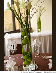 Fruit  wedding centerpiece with limes in clear vase with twigs and calla lillies