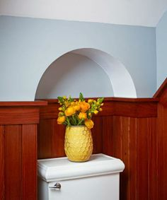 A pale blue painted arch crowns a toilet alcove and creates more room for the bathroom necessity.| Photo: Nathan Kirkman | thisoldhouse.com