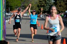 Description of . Ryan Otto and his wife Temple Hayles raise their arms high as they cross the finish line of the 1/2 marathon in the 9th annual Colfax Marathon May 18, 2014. The 26.2 mile Marathon runs through Denver's iconic landmark Mile High Stadium (twice), Sloan's Lake, City Park, Colfax Avenue through Lakewood and Aurora. The Marathon started and finished in City Park where runners enjoyed the rest of the day listening to music by Chris Daniels and the Kings. (Photo by John Leyba/The…