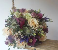 Stunning roses mixed with beautiful plum hellebores and textural sea holly and delicate astrantia make this a beautiful wedding bouquet.