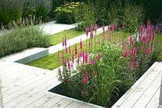 Strakke tuin met gras en roze bloemen
