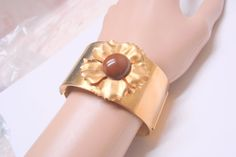 JoysShop is pleased to submit for your consideration this wonderful wide, chunky, hinged bangle bracelet, featuring a large brown Lucite stone and a bright goldtone patina.... #vintage #jewelry