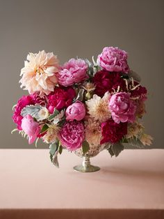 lush pink peony and peachy dahlia arrangement with astilbe, protea and dusty miller