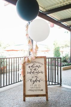 Custom wedding signage - hand lettered calligraphy on a wooden easel. Giant balloons make anything more fun :)  Clara Doyle Designs | www.claradoyle.com | www.instagram.com/claradoyledesigns