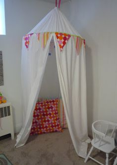 indoor play tent from hula hoop, sheet, and fabric banners. How cute is that?!