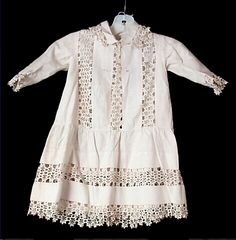 1885 Boy's Dress Culture: American Medium: cotton, piqué, mother of pearl Ivory cotton pique, with small basket-weave pattern; machine-sewn; dropped waist, with calf-length gathered skirt; straight bodice; long crescent shaped sleeves; narrow bermuda-style collar; ivory ric-rac manipulated into snowflake-like shapes is inset in three vertical bands down bodice front, horizontal band midway down skirt. Source…