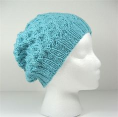 This very feminine hat is hand knit in a scallop pattern with an aqua merino yarn. It is slouchy but not baggy.   The yarn is a four ply merino wool treated to be machine washable and is softer than regular wool. It is also warmer than synthetic yarn and eco-friendly!   If you would like this hat in a different color or yarn, just let me know as I love to do custom work. There are also a LOT of other hats in my gallery, so please take a look.    Item #327 - Scallop hat  Fibe r- Superwash…