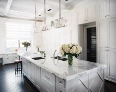 White and marble kitchen with dark stained wooden floors, two sinks and a grand light feature. The black door is quite clever too. By Jamie Herzlinger via Marcus Design