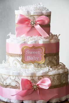 This unique Pink and Gold princess diaper cake will make a perfect addition to baby shower decor or just as a token of love for a friend to welcome the little princess!!  Ivory Gold scroll ribbon with pink satin ribbon embellished with bows and rhinestone make it so elegant and unique. Cake structure is secured with wooden dowel and cake board. ** Size 1 diapers - Pampers swaddlers ** Premium Ribbons ** Cake Board ** Paper Shred ** 100% Usable diapers ** Individually wrapped ready to…