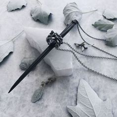 Winter dark wonderland... Long spike stingray barb pendant stabbing through an antique silver wildflower wreath ring. Inspired by memento mori and curiosities and dark romanticism. Perfect Game of Thrones jewellery. Shop more unique dark jewellery now.